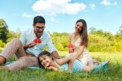 Familia en parque Padres felices y niño jovenes que se relajan al aire libre Imagen de archivo