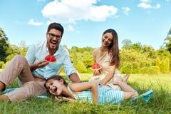 Familia en parque Padres felices y niño jovenes que se relajan al aire libre Foto de archivo libre de regalías