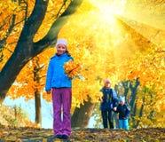 Familia en parque risueno del arce del otoño foto de archivo