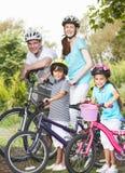 Familia en paseo del ciclo en campo Imágenes de archivo libres de regalías