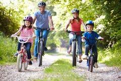 Familia en paseo del ciclo en campo Fotos de archivo libres de regalías