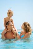 Familia en piscina. La hija se sienta en hombro de los padres Foto de archivo libre de regalías