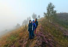Familia en prado brumoso de la montaña del rocío de la mañana Imagenes de archivo