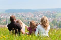 Familia en prado en resorte o comienzo del verano Imagenes de archivo