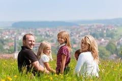 Familia en prado en resorte o comienzo del verano Fotos de archivo libres de regalías