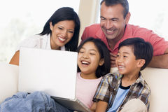 Familia en sala de estar con la computadora portátil