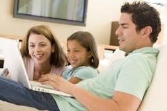 Familia en sala de estar con la computadora portátil Foto de archivo libre de regalías