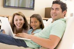 Familia en sala de estar con la computadora portátil fotografía de archivo libre de regalías