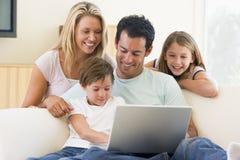 Familia en sala de estar con la sonrisa de la computadora portátil Fotos de archivo libres de regalías