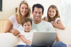 Familia en sala de estar con la sonrisa de la computadora portátil