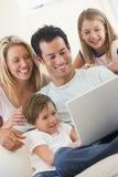 Familia en sala de estar con la sonrisa de la computadora portátil Fotografía de archivo libre de regalías