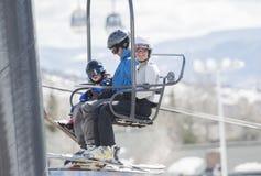 Familia en Ski Lift con el niño joven que va para arriba la montaña Vestido con seguridad con los cascos imagen de archivo libre de regalías