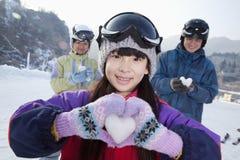 Familia en Ski Resort, hija que muestra el corazón de la nieve Fotografía de archivo libre de regalías