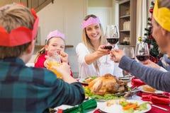 Familia en sombrero del partido que tuesta en la cena de la Navidad Fotos de archivo