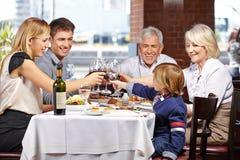 Familia en tintinear del restaurante Fotografía de archivo