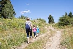 Familia en un alza de naturaleza en las montañas Imagen de archivo libre de regalías