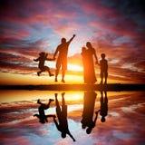 Familia en un fondo de la puesta del sol magnífica Foto de archivo libre de regalías