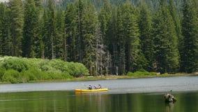 Familia en un kajak en un lago cerca del bosque almacen de metraje de vídeo