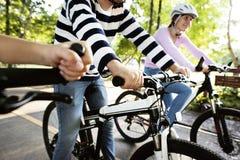 Familia en un paseo de la bici en el parque imagenes de archivo