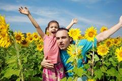 Familia en un paseo en campo de los girasoles Fotografía de archivo libre de regalías