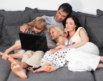 Familia en un sofá con la computadora portátil foto de archivo