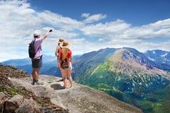 Familia en un viaje que camina en la montaña Imagenes de archivo