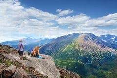 Familia en un viaje que camina en las montañas Imagenes de archivo