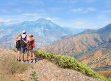 Familia en un viaje que camina en las montañas Imágenes de archivo libres de regalías
