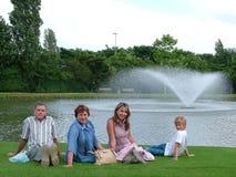 Familia en una hierba bajo el cielo azul Imagen de archivo libre de regalías