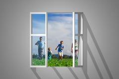 Familia en ventana Foto de archivo libre de regalías
