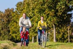 Familia en viaje de la bicicleta en parque Fotos de archivo