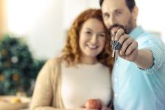 Familia encantada que lleva a cabo llaves a un nuevo plano Imágenes de archivo libres de regalías