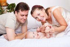 Familia encantadora en cama Imagenes de archivo