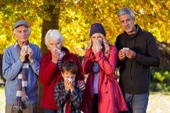 Familia enferma que se coloca en el parque Fotos de archivo