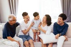 Familia extensa asiática feliz que se sienta en el sofá junto, presentando para las fotos del grupo foto de archivo libre de regalías