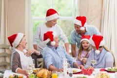 Familia extensa feliz en el sombrero de santa que habla junto Fotos de archivo