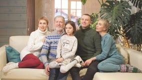 Familia extensa feliz que se sienta en el sofá junto almacen de video