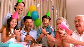 Familia extensa que celebra cumpleaños junto en el sofá metrajes