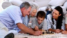 Familia extensa que juega al ajedrez junto almacen de metraje de vídeo