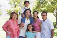 Familia extensa que se coloca al aire libre sonriente Imágenes de archivo libres de regalías