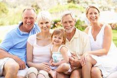 Familia extensa que se relaja en jardín Imagen de archivo libre de regalías
