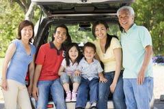 Familia extensa que se sienta en la puerta posterior del coche Imágenes de archivo libres de regalías