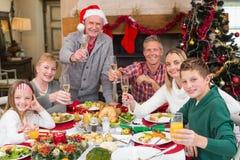 Familia extensa que tuesta en la cena de la Navidad Imagen de archivo