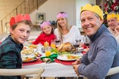 Familia extensa sonriente en sombrero del partido en la tabla de cena Imágenes de archivo libres de regalías
