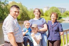 Familia famHappy feliz que pasa tiempo al aire libre en un día de verano soleado mamá, papá, abuela y dos muchachos imagenes de archivo