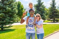 Familia feliz afroamericana: padre, mamá y bebé negros en la naturaleza Utilícelo para un concepto del niño, el parenting o del a Imagen de archivo libre de regalías