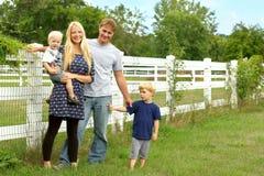 Familia feliz afuera por el pasto del caballo Imagenes de archivo