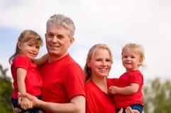 Familia feliz al aire libre en rojo Fotos de archivo