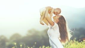 Familia feliz al aire libre la madre lanza el bebé para arriba, la risa y el playi imagen de archivo libre de regalías