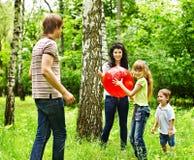 Familia feliz al aire libre que juega la bola. Fotografía de archivo